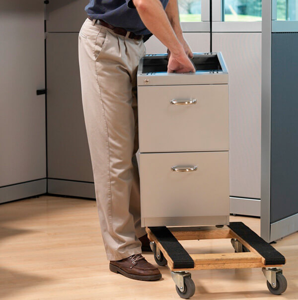 Man moving an office metal file cabinet